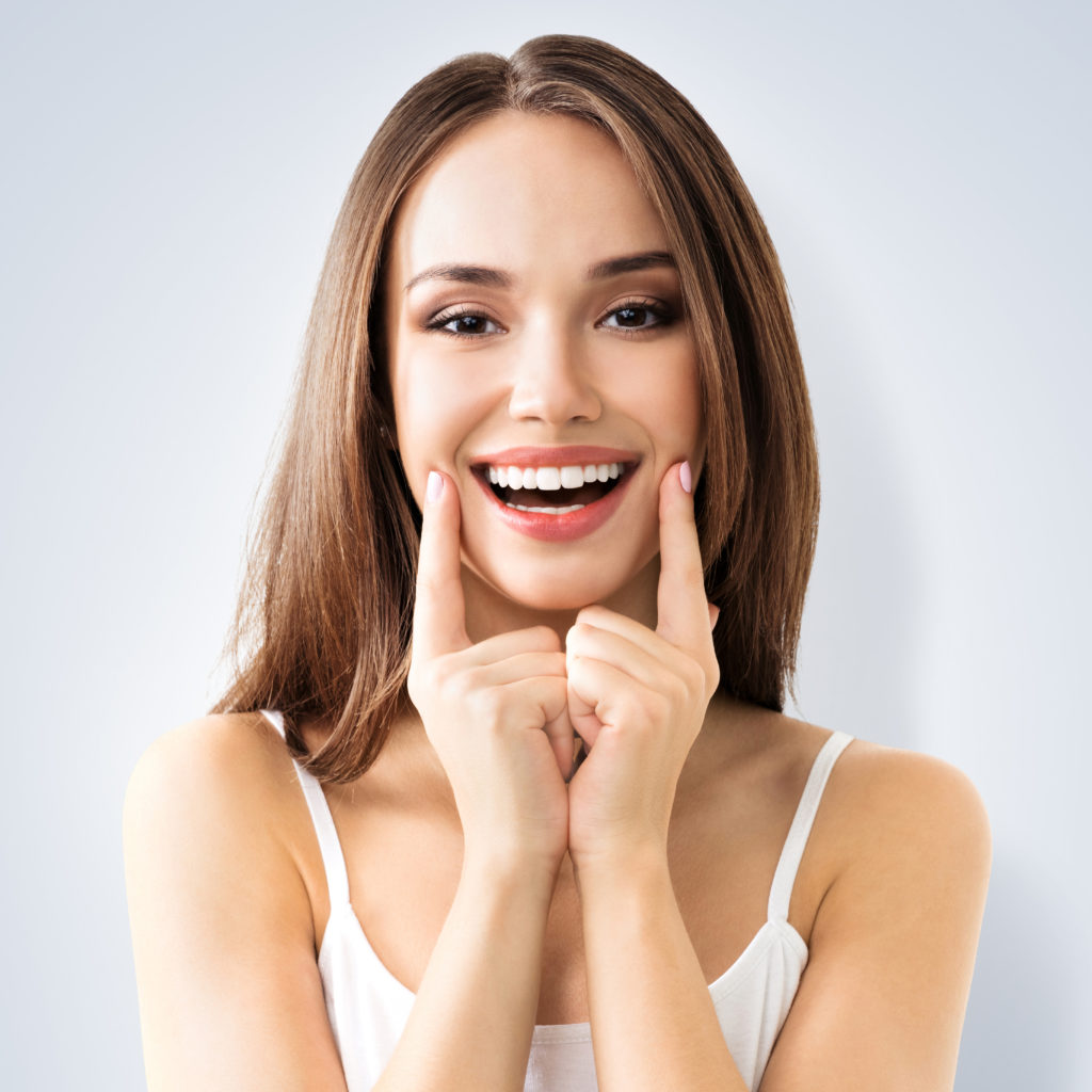 woman pointing at cheeks smiling